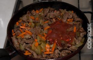 жареное мясо с луком, морковью, соленым огурцом и томатным соусом